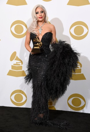 """Lady Gaga poses in the press room with the award for best traditional pop vocal album for """"Cheek to Cheek"""" at the 57th annual Grammy Awards at the Staples Center on Sunday, Feb. 8, 2015, in Los Angeles. (Photo by Chris Pizzello/Invision/AP)"""